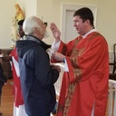 Feast day of St. Blaise - Deacon Nate blessing the throat of a parishioner - Feb 2020